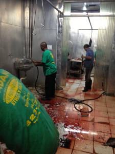Workers at Al Madani sweep blood and water off the slaughterhouse floor.