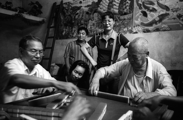 A mahjong game, for low stakes, in Jiangmei. At left, Chen Huajia, a retired village official. 2009.