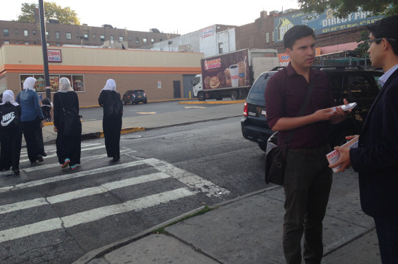 Carlos Menchaca speaks to a potential constituent in Sunset Park as a group of young women in hijab pass by.  Photo by Esther Wang.