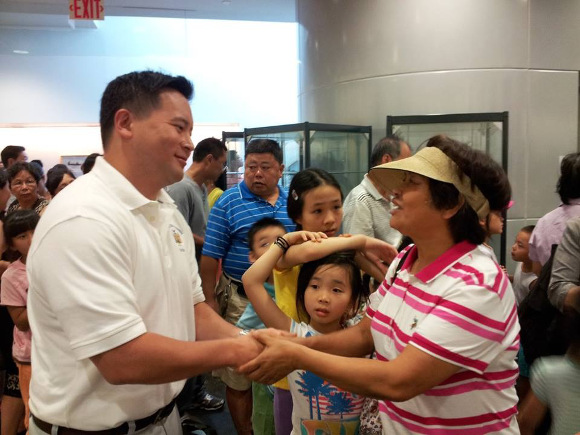 Assemblyman Ron Kim greeting parents and kids during a back-to-school book bag giveaway event, August 2013 at the Queens Library in Flushing. About 350~400 people attended the event.