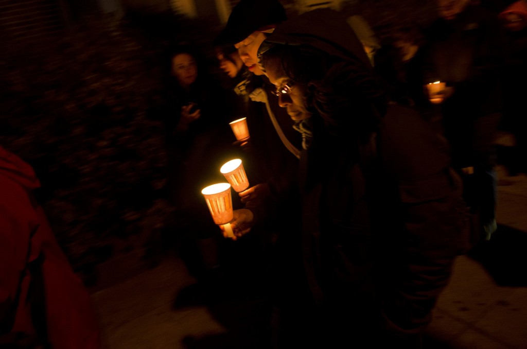 Waxed paper cups served as makeshift candle holders at the evening vigil in Queens. Photo by Skyler Reid.