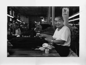 A man working in a garment factory on Canal Street. 1979-1982. Courtesy of Paul Calhoun, Museum of Chinese in America (MOCA) Collection.
