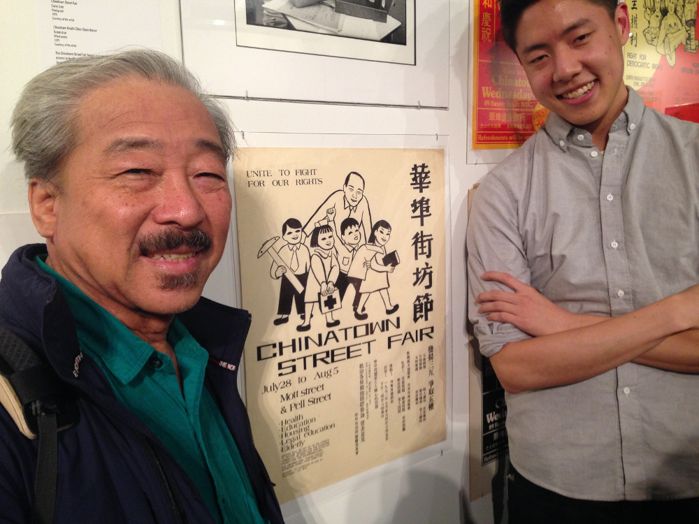 Artist Bob Lee next to a poster he designed for the first Chinatown Street Fair in 1971, along with curator Ryan Wong. Photo by Esther Wang.