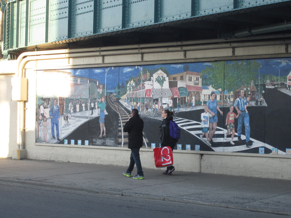 A couple walks by a mural of the neighborhood. Credit: Marwa H. Helal.