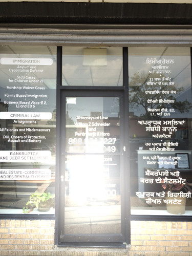 English and Punjabi texts are printed on the glass wall of Pert Hora's office. Photo by Sonny Singh