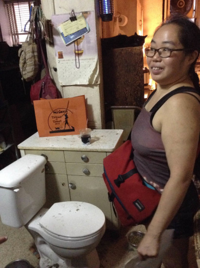 Betty Eng showing the toilet in her living room. Photo by Rong Xioaqing
