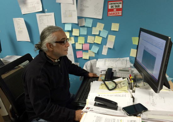 Javaid at his desk in the NYTWA office. While he no longer has dreadlocks, his hair is still long. Photo by Sonny Singh