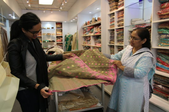 Nasreen shows her customer, Mahima, a traditional Bangladeshi saree.