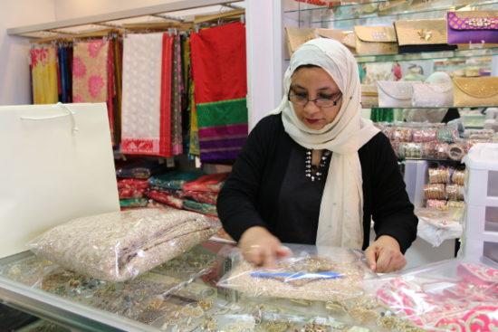 Nasreen's assistant packs a customer's lehenga.